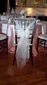 Elegant organza chair caps in ivory combined with satin blush tablecloths