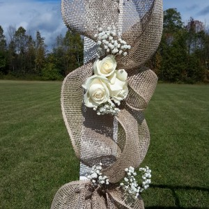 Roses and babies breath with burlap wrapped around a large arbor