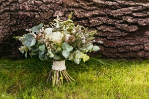 wedding bouquet with roses and other flowers on green grass and wooden texture