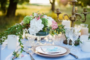 beautiful wedding table decorated with fresh flowers, candles and an invitation