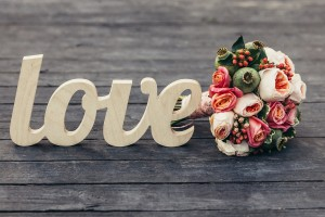 The word love with wedding bouquet on wooden background